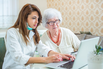 Nurse and senior patient analyzing medical results on laptop. Home care concept.