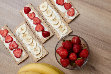 Healthy food. Fruit cut into bread and biscuits. A delicious dessert. Strawberry. Bananas. Fruits on a wooden background.Healthy food. Fruit cut into bread and biscuits.