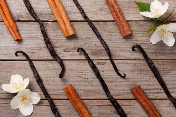 Vanilla sticks and cinnamon with flower and leaf on a old wooden background