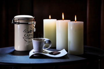 Cup of coffee costs on a table on a background of burning candles