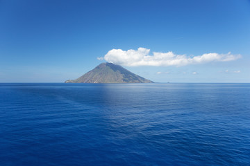 Isolated cloud above Stromboli Island. The volcano has erupted many times and is constantly active with minor eruptions. Mt. Stromboli has been in almost continuous eruption for the past 2,000 years.