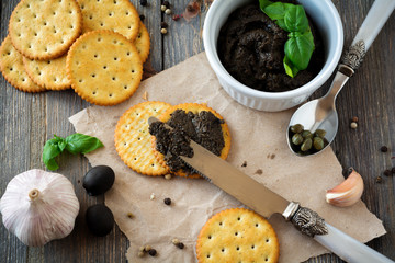 Tapenade, traditional Provence dish with olives,cracker and basil on an old wooden table background. Selective focus.Top view..