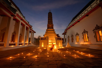 Asian woman wearing traditional thai culture with light candle in temple on after sunset,vintage style,Thailand