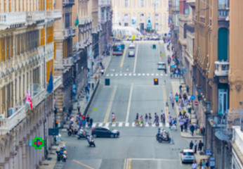 Blurred image of people and traffic moving in crowded city street. Art toning abstract urban background. Crowd of traffic anonymous people walking on busy city street.