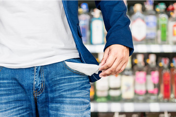 Man showing his empty pocket on blur alcohol background.