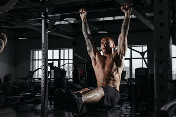 Shirtless muscular bearded male doing exercises on horizontal bar in a gym club.