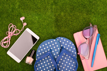 Female fashion accessories - flip flops, smart phone with headphones, note pad, sunglasses on the grass