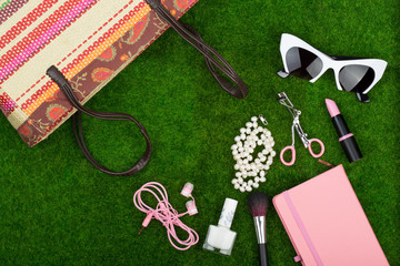 Female fashion accessories - bag, note pad, sunglasses, headphones, lipstick and other essentials on the grass