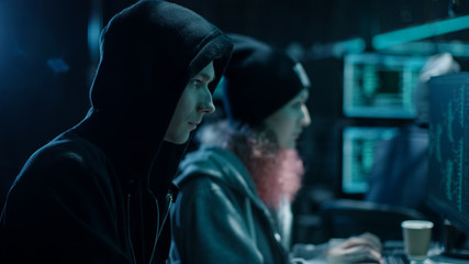 Close-up Shot of Internationally Wanted Boy and Girl Hackers Team Working on Their Computers. Place is Hacker's Den with Dark atmosphere.