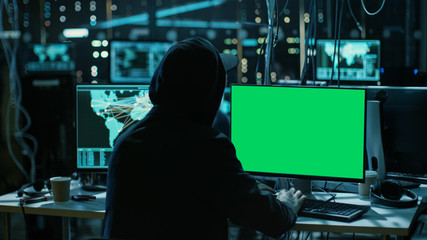 Teenage Hacker is Working With his Computer with Green Screen Mock-up Display Infect Servers and Infrastructure with Malware. His Hideout is Dark, Neon Lit and Has Multiple displays.