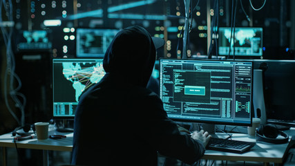 Teenage Hacker Working with His Computer Infecting Servers and Infrastructure with Malware. His Hideout is Dark and Has Multiple displays.
