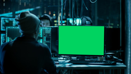 Shot of Teenage Hacker Working with Green Screen Mock-up Display Infecting Servers and Infrastructure with Malware. His Hideout is Dark, Neon Lit and Has Multiple Displays. Good as a Template.