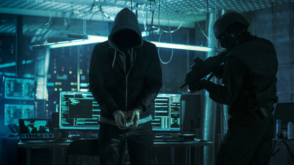 Handcuffed Masked Hacker is Standing and Guarded by Fully Armed Special Forces Soldier. They're in Hacker's Hideout Basement with Multiple Operating Displays.