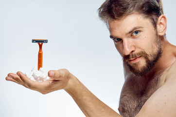 Young guy with a beard on a white isolated background holds a razor and foam for shaving