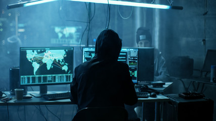 Team of Internationally Wanted Teenage Hackers Infect Servers and Infrastructure with Ransomware. Their Hideout is Dark, Neon Lit and Has Multiple displays.