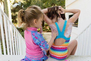 Children sitting on stairway, applying sun tan lotion on each other, rear view, close up