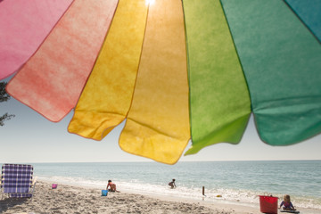 Looking through rainbow colour parasol at children playing by waters edge