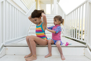 Children sitting on stairway, applying sun tan lotion on each other