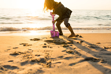 Child digging sand by waters edge with spade