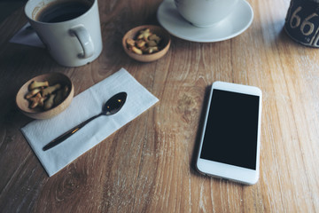 Mockup image of white mobile phone with blank black screen , coffee cups and snacks on vintage wooden table in cafe