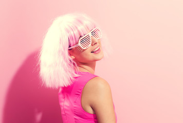 Wall Mural - Beautiful woman in a bright pink wig on a pink background