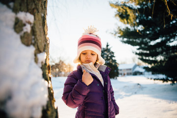 Young girl looking at thumb by tree in snowy landscape