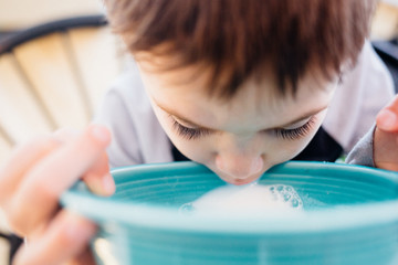 Boy drinking milk from blue cup, portrait