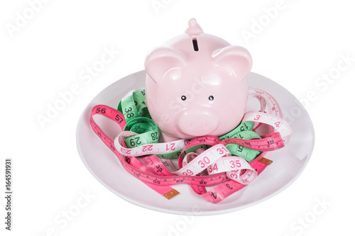 Pink piggy bank amongst tangled measuring tapes