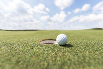 golf ball on lip of cup. Golf ball on green grass in golf course