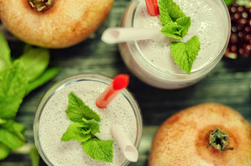 Pomegranate smoothies with mint in glass on a black background