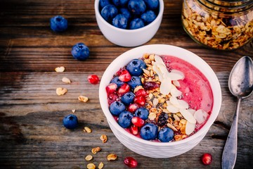 Raspberry smoothie bowl with granola, chia seeds, almonds, fresh blueberries and pomegranate