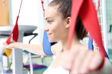 Rehabilitacja kończyn górnych. Kobieta ćwiczy ręce na podwieszkach odciążających.