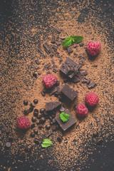Pieces of dark chocolate, powder, drops and raspberries. Food dessert background.