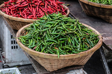 Green and red peppers in wooden baskets for sale in outdoor markets.