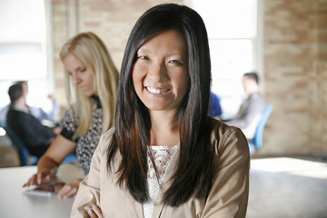 Asian professional woman smiling with creative office group