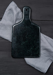 Dark marble cutting board with napkin on black wooden background, top view