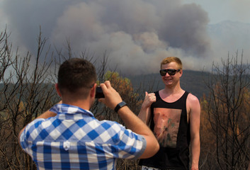 A tourist poses for his friend's picture with a forest fire in the background at Lustica peninsula near Tivat