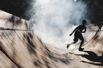 Teenage Boy Running On Skateboard Park During Foggy Weather
