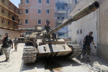 A Member of the Libyan army's special forces gestures as he sits atop a tank during clashes with Islamist militants in the militants' last stronghold in Benghazi,