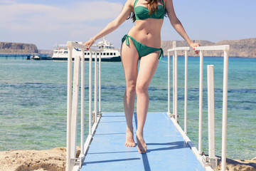 young Caucasian girl in a green swimsuit on the blue pier, by background blue Ionian sea, Balos, Greece