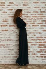 Full Length Of Beautiful Woman In Black Dress Standing Against Brick Wall