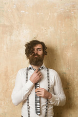 Hipster in shirt and suspenders with musical tie