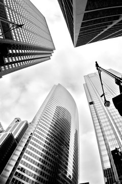 Urban background. Modern architecture background. Glass skyscrapers against cloudy sky in the city of Chicago, Illinois, USA. Black and white abstract upward view of downtown skyscrapers.