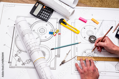 Mechanical engineer with work at technical drawings and work