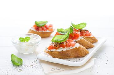 Bruschetta with cream cheese, tomatoes and basil