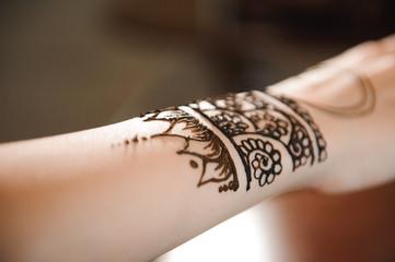 Master mehndi draws henna on a female hand.