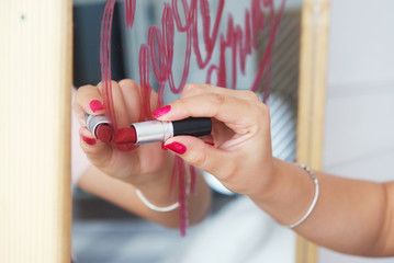 A female hand writes on a mirror by lipstick