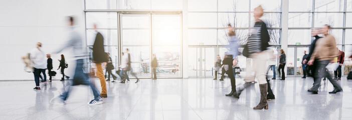 Fototapete - blurred people commuting traveling walking in a modern hall