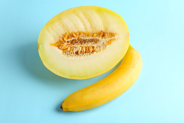 Half of juicy melon and banana on color background. Sex concept
