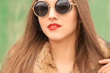 Beautiful young woman with bright lips and sunglasses, closeup